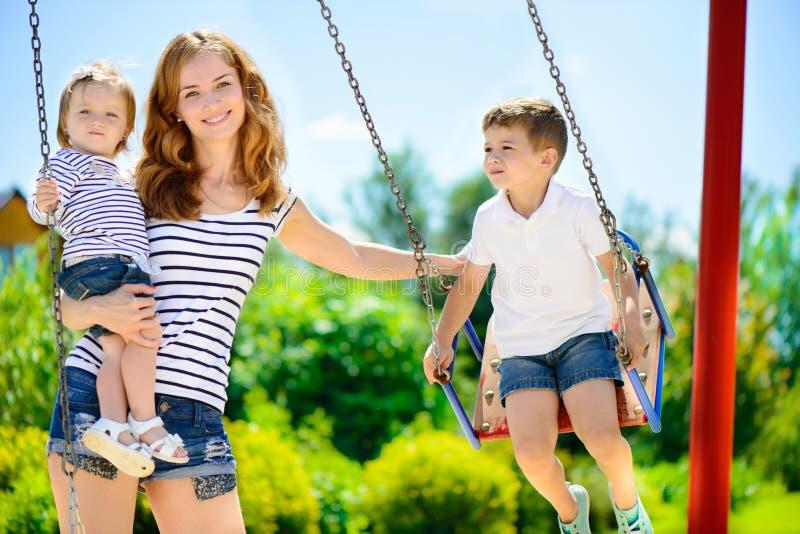 Glückliche Familie auf Spielplatz lizenzfreies stockbild