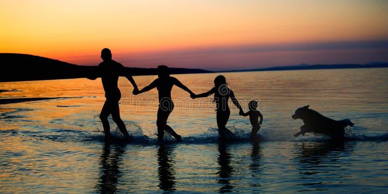 Glückliche Familie auf Strandsonnenuntergang lizenzfreie stockbilder