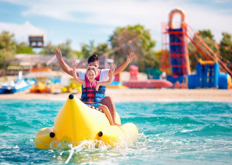 Glückliche Familie, begeisterter Vater und Sohn, die den Spaß, fahrend auf Bananenboot während der Sommerferien hat stockbild