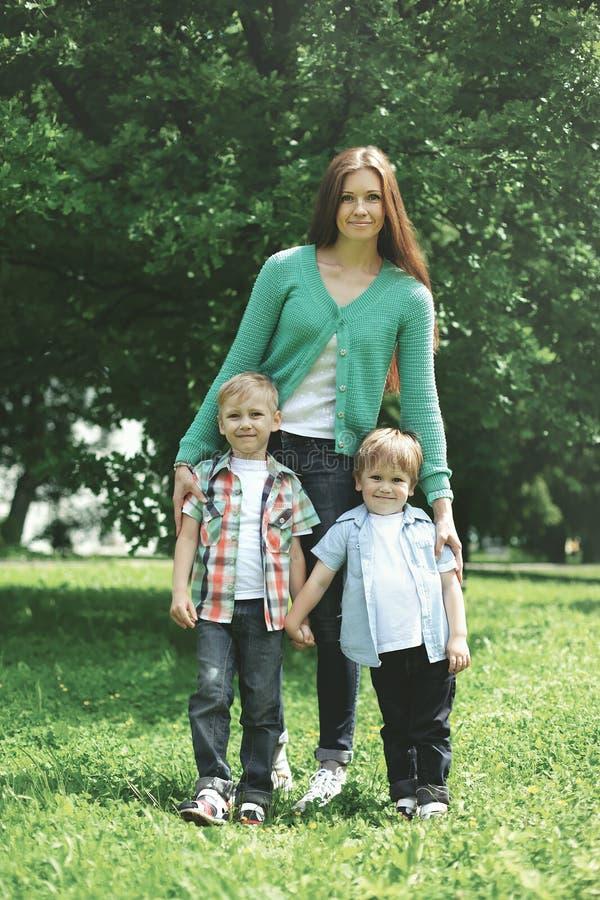 Glückliche Familie! Bemuttern Sie mit zwei Kindersohnwegen auf Natur lizenzfreie stockfotografie