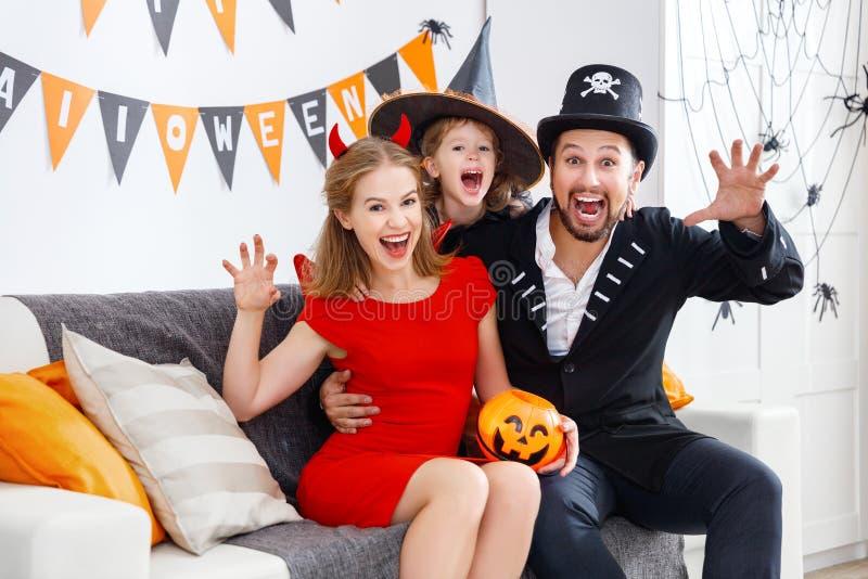 Glückliche Familie in den Kostümen, die zu Hause zu Halloween fertig werden stockbild