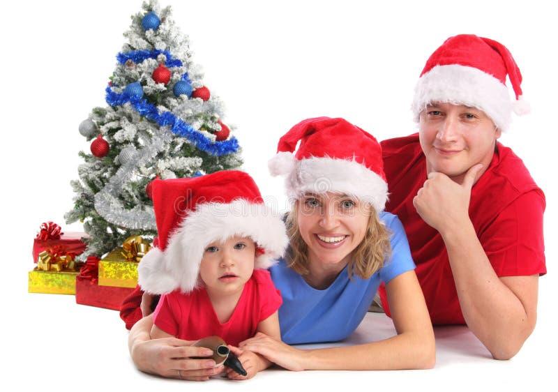 Glückliche Familie in den Weihnachtshüten lizenzfreie stockfotos