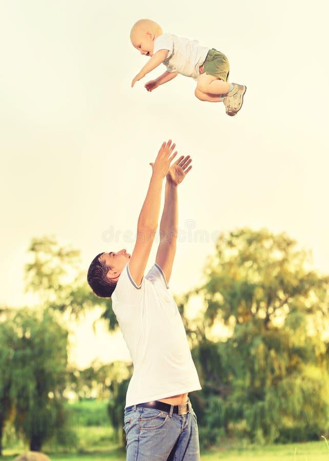Glückliche Familie in der Natur Vati wirft oben Babykind lizenzfreies stockbild