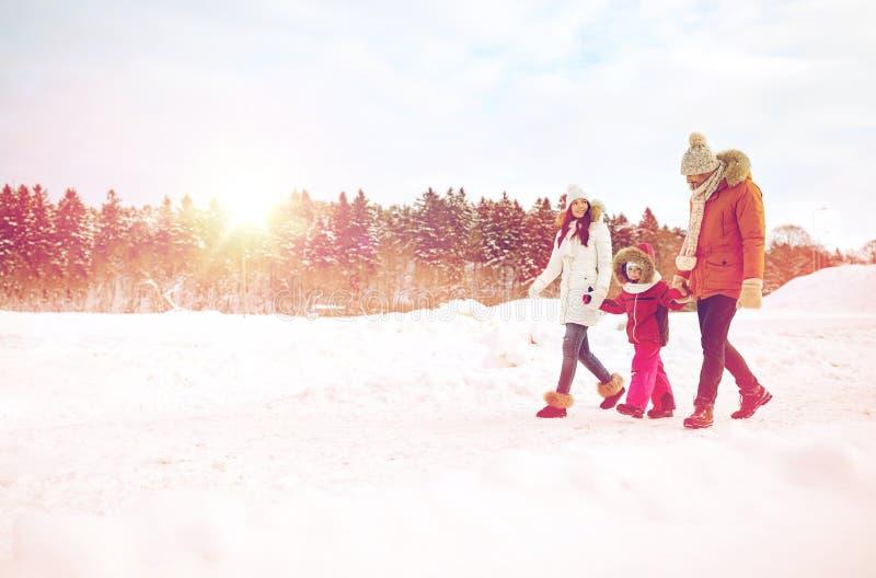 Glückliche Familie in der Winterkleidung draußen gehend lizenzfreies stockfoto