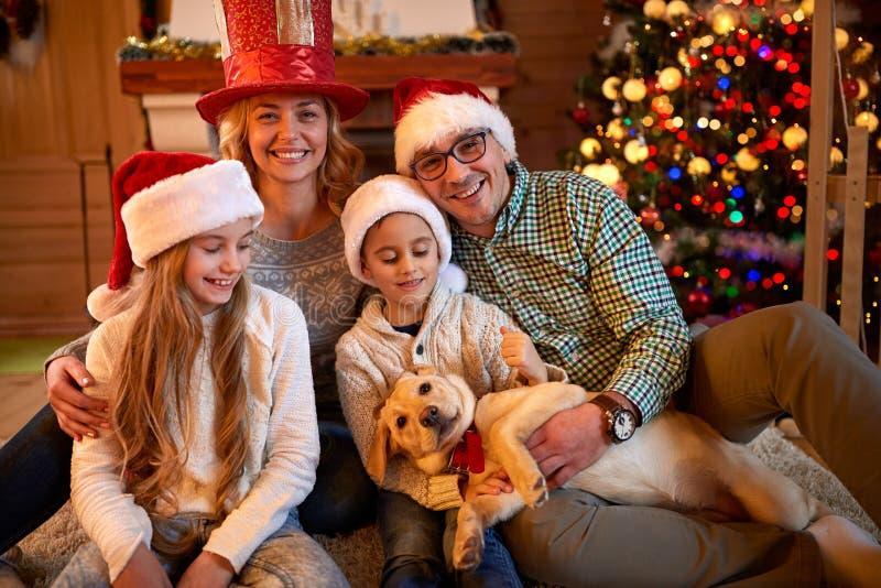 Glückliche Familie des Porträts am Weihnachtsabend mit Hund stockfoto