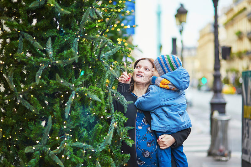 Glückliche Familie des schauenden zwei Weihnachtsbaums lizenzfreies stockbild