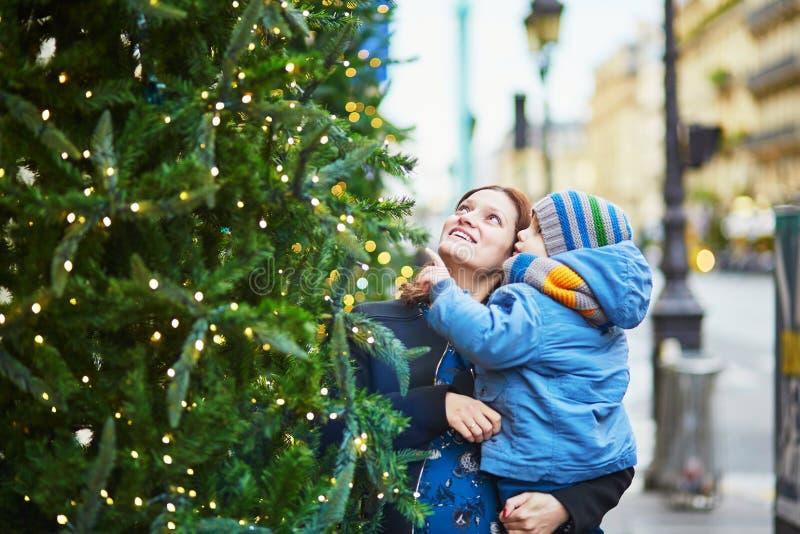 Glückliche Familie des schauenden zwei Weihnachtsbaums stockbild