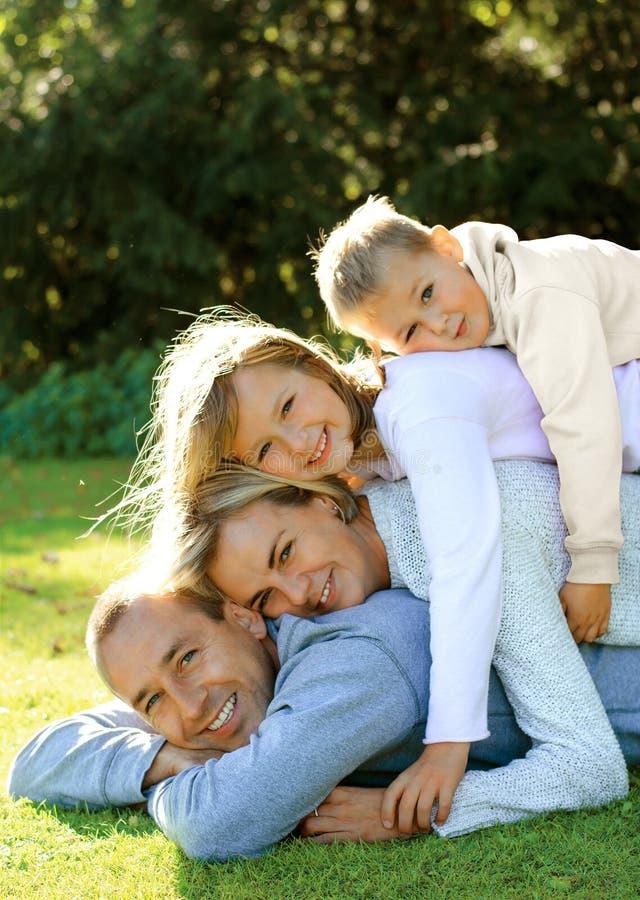Glückliche Familie, die auf dem Gras liegt lizenzfreies stockbild