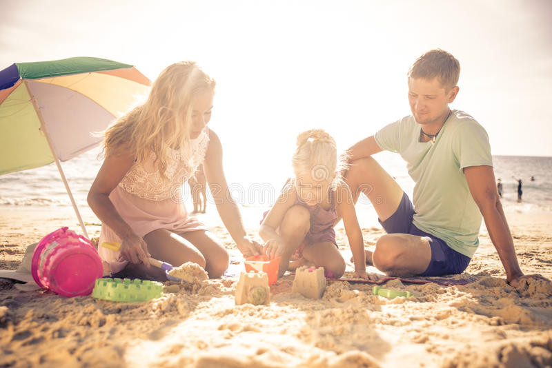 Glückliche Familie, die auf dem Strand spielt stockfotos