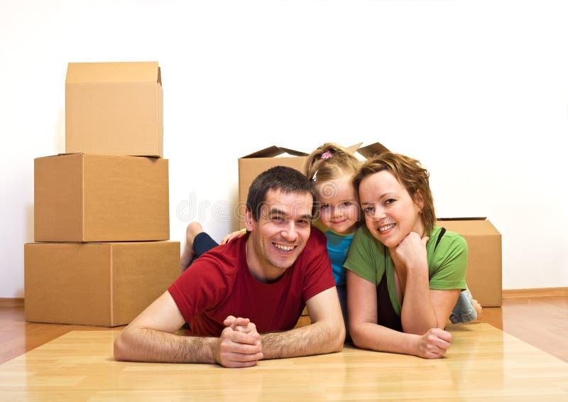 Glückliche Familie, die auf den Fußboden in ihrem neuen Haus legt lizenzfreies stockfoto