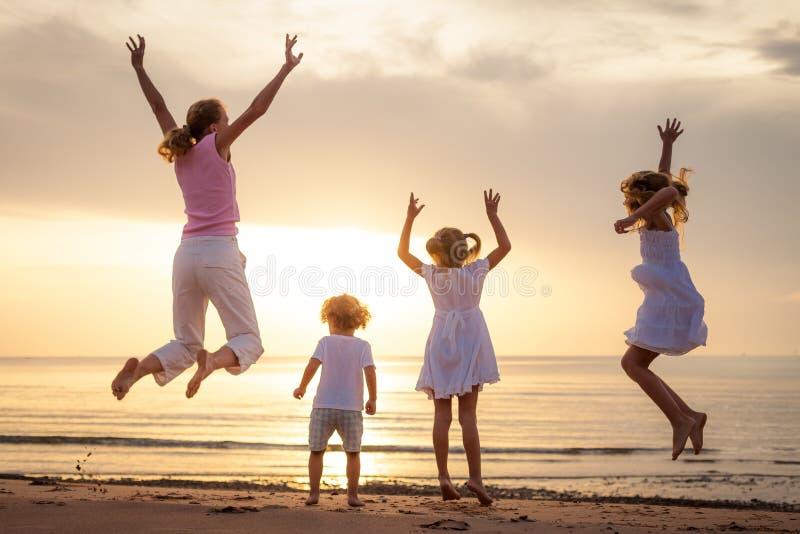 Glückliche Familie, die auf den Strand springt stockfotos