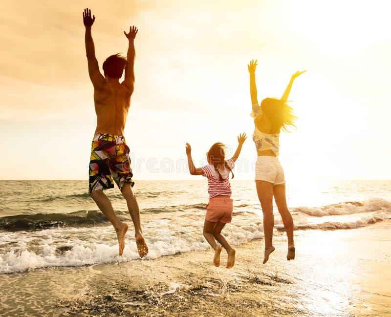 Glückliche Familie, die auf den Strand springt lizenzfreie stockbilder