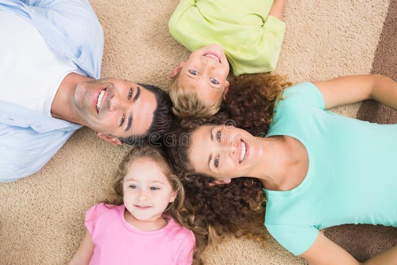 Glückliche Familie, die auf der Wolldecke in einem Kreis liegt stockbild
