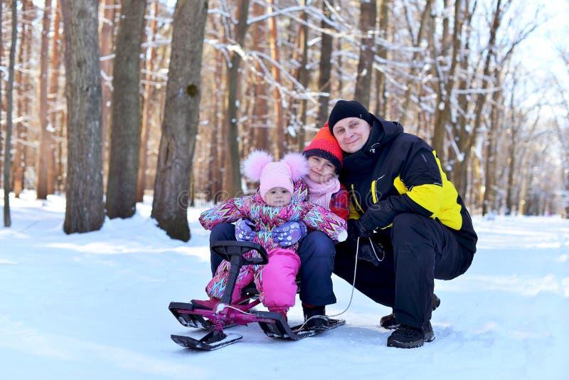 Glückliche Familie, die auf einem Schlitten im Winter sitzt lizenzfreie stockfotos