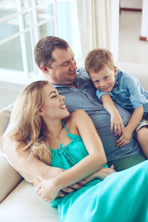 Glückliche Familie, die auf einem Sofa stillsteht lizenzfreie stockbilder