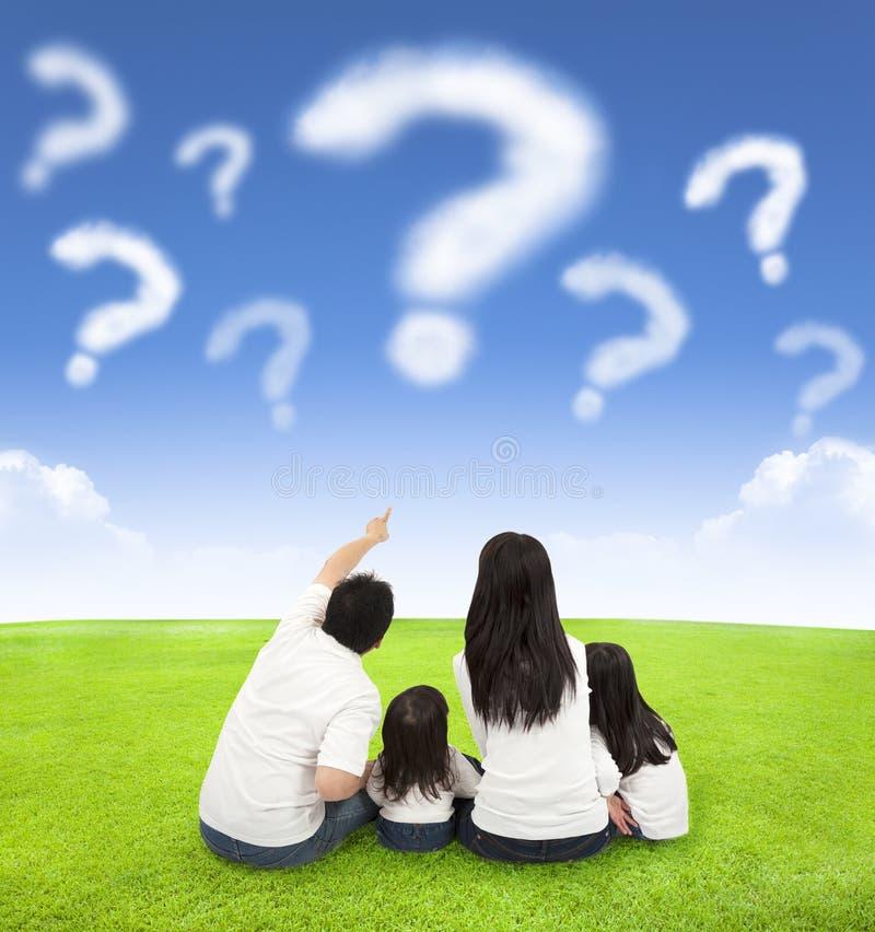 Glückliche Familie, die auf einer Wiese mit Frage von Wolken sitzt lizenzfreies stockbild