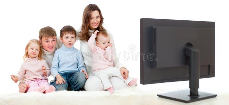 Glückliche Familie, die auf Fußboden und überwachendem Fernsehapparat sitzt stockbilder