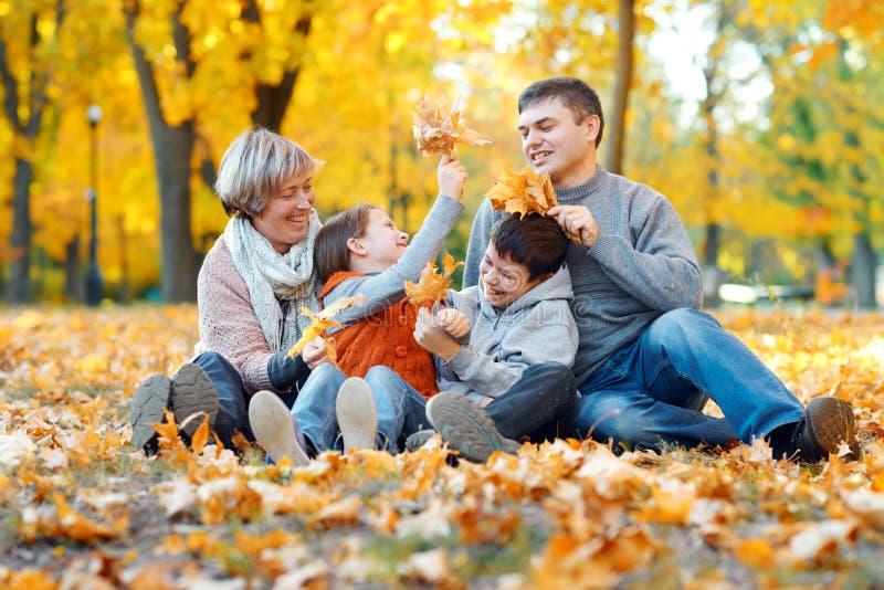 Glückliche Familie, die auf gefallenen Blättern sitzt, Spaß im Herbststadtpark spielt und hat Kinder und Eltern, die zusammen ein lizenzfreie stockfotos
