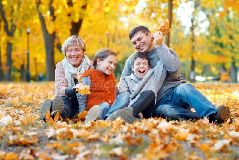 Glückliche Familie, die auf gefallenen Blättern sitzt, Spaß im Herbststadtpark spielt und hat Kinder und Eltern, die zusammen ein lizenzfreie stockbilder