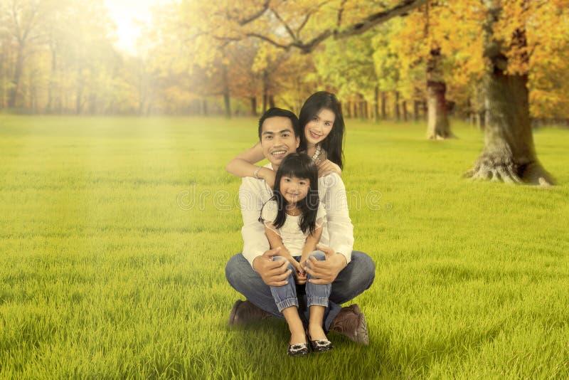 Glückliche Familie, die auf Gras an der Herbstsaison sitzt lizenzfreies stockbild