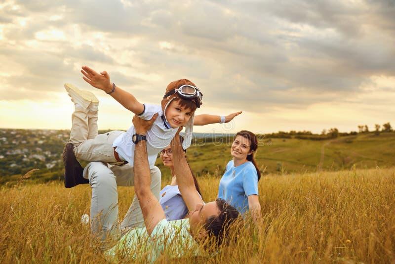 Glückliche Familie, die auf Gras in der Natur bei Sonnenuntergang spielt lizenzfreie stockfotografie