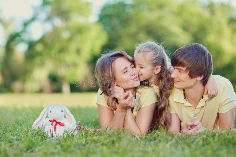 Glückliche Familie, die auf Gras im Park liegt lizenzfreies stockbild