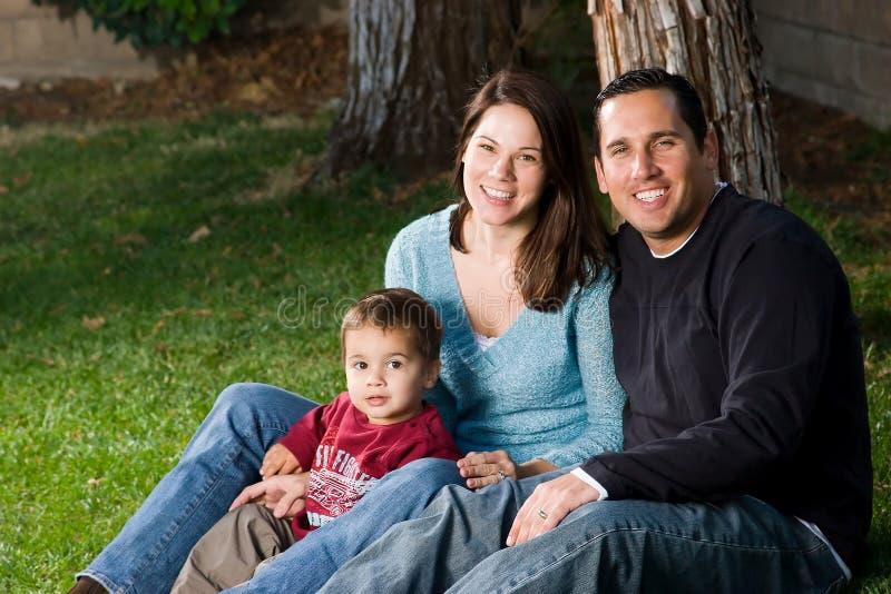 Glückliche Familie, die auf Gras sitzt stockbild