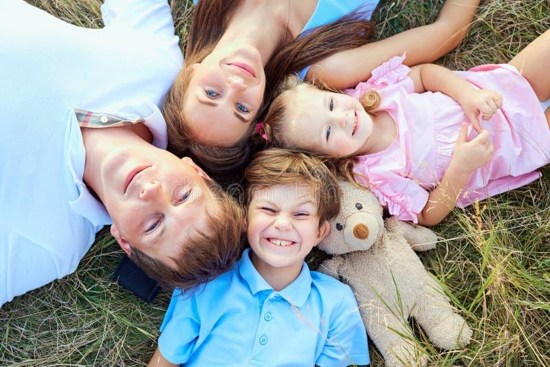Glückliche Familie, die auf Grasgroßaufnahme von oben liegt stockfotos