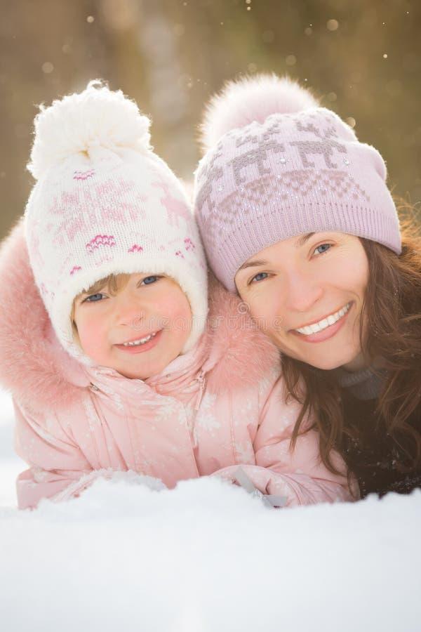 Glückliche Familie, die auf Schnee liegt lizenzfreie stockfotos