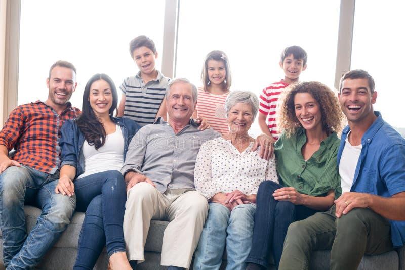 Glückliche Familie, die auf Sofa sitzt stockbild