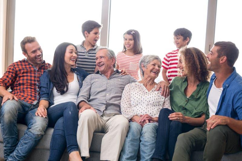 Glückliche Familie, die auf Sofa sitzt lizenzfreie stockfotografie