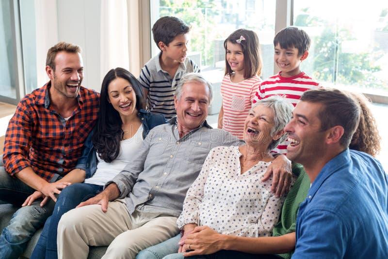Glückliche Familie, die auf Sofa sitzt lizenzfreie stockfotos