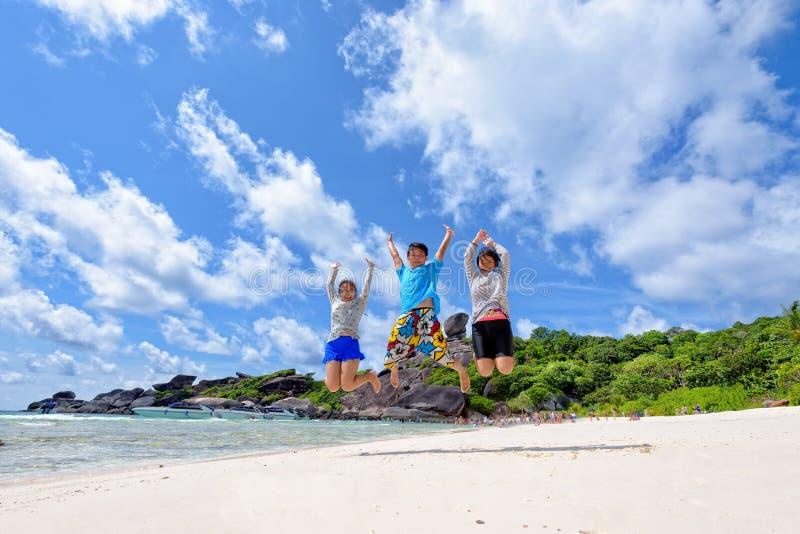 Glückliche Familie, die auf Strand in Thailand springt stockbilder