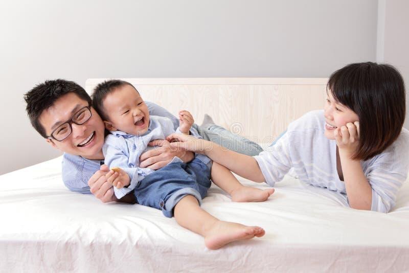Glückliche Familie, die auf weißem Bett spielt lizenzfreie stockfotografie
