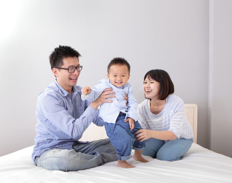 Glückliche Familie, die auf weißem Bett spielt stockbild