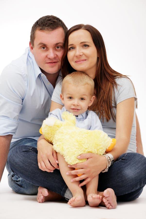 Glückliche Familie, die auf weißem Hintergrund aufwirft. stockbilder