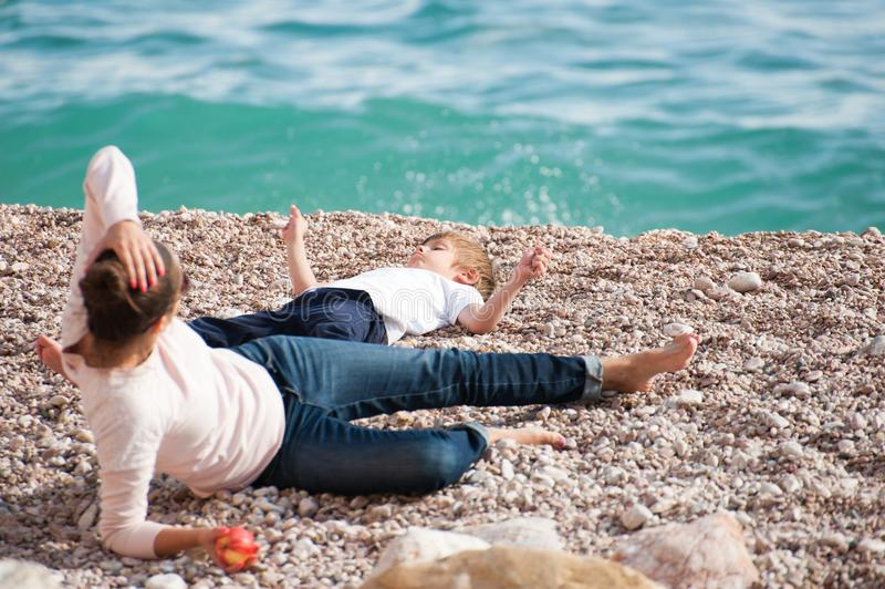 Glückliche Familie, die aus dem stillstehenden Lügen der Mutter und des Kindes auf Seestrand am Sommertag besteht stockbilder