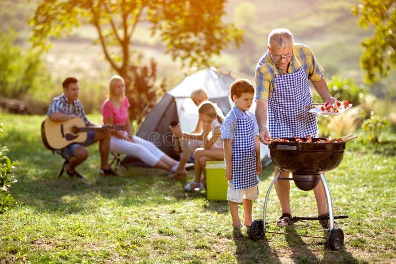 Glückliche Familie, die bbq kampiert und herstellt lizenzfreie stockfotos