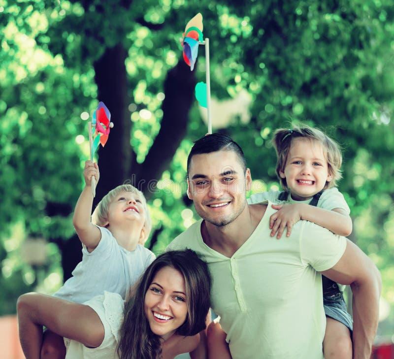 Glückliche Familie, die bunte Windmühlen spielt lizenzfreie stockfotografie