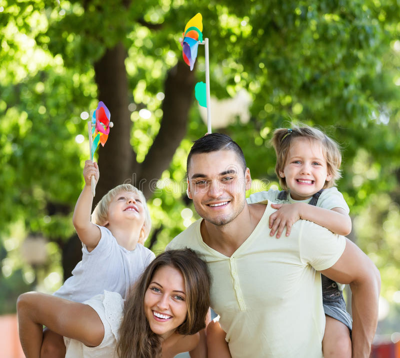 Glückliche Familie, die bunte Windmühlen spielt lizenzfreies stockbild