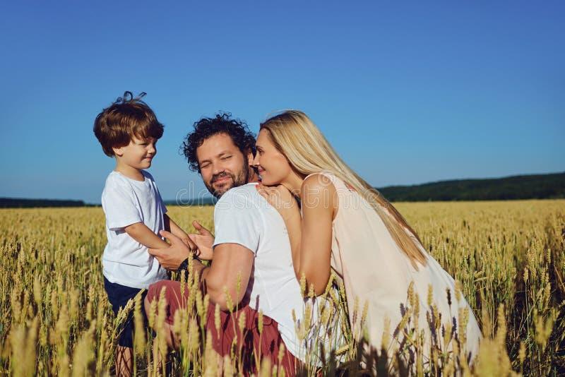 Glückliche Familie, die den Spaß spielt auf dem Gebiet hat stockfotos