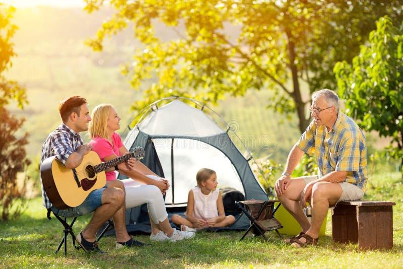 Glückliche Familie, die an der Landschaft kampiert stockfotografie