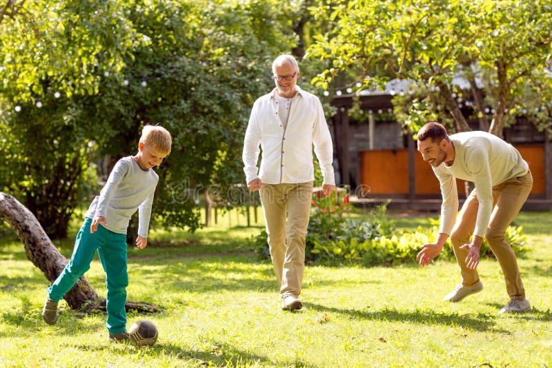 Glückliche Familie, die draußen Fußball spielt stockfotografie