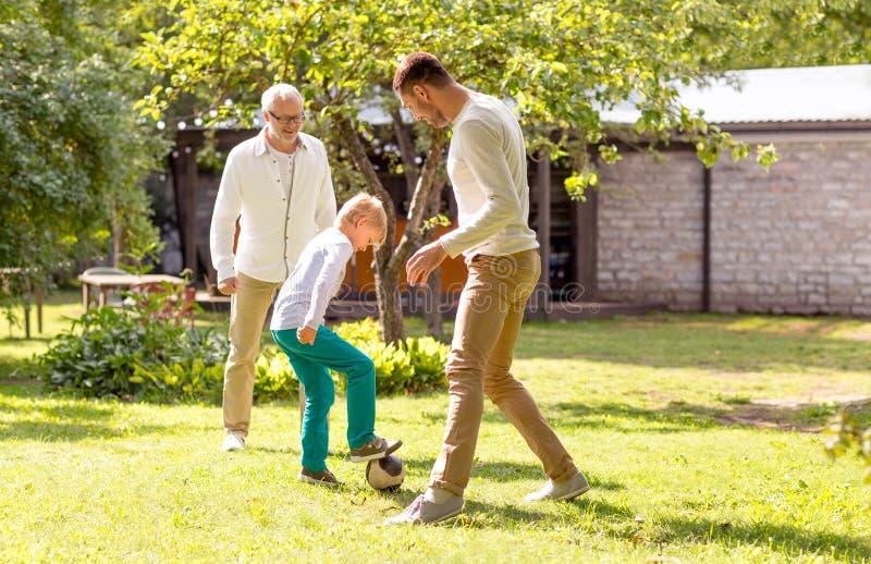 Glückliche Familie, die draußen Fußball spielt stockfotos