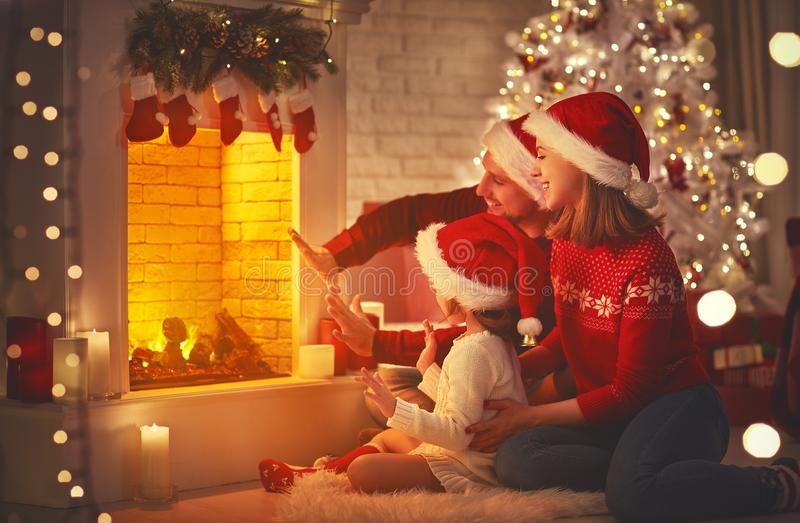 Glückliche Familie, die durch Kamin auf Weihnachtsabend sitzt lizenzfreies stockbild