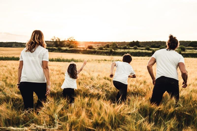 Glückliche Familie, die durch die Landschaft läuft Familie, die Spaßfeld hat stockfotografie