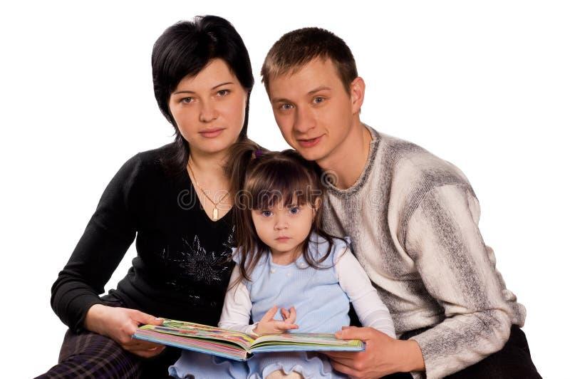 Glückliche Familie, die ein Buch liest stockbilder