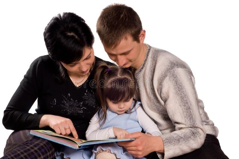 Glückliche Familie, die ein Buch liest lizenzfreie stockbilder