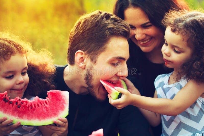 Glückliche Familie, die ein Picknick im grünen Garten hat Lächelnde und lachende Leute, die Wassermelone essen Biokostkonzept Ein stockbilder