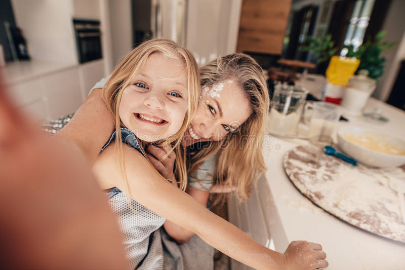Glückliche Familie, die ein selfie in der Küche nimmt lizenzfreie stockfotos